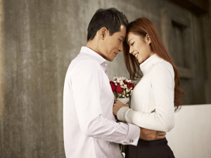 Asian couple holding a flower