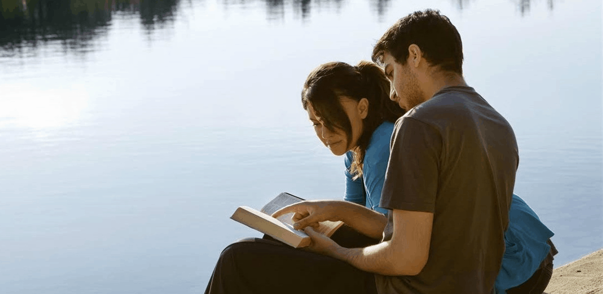 Christian couple reading the Bible at the lakeside