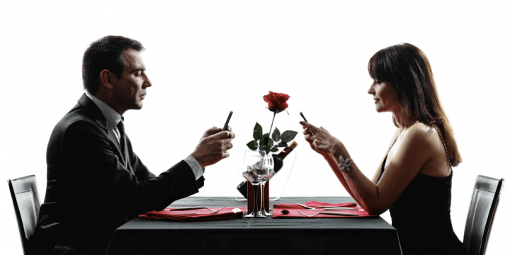 A couple texting on phone while dating in real life