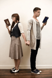 A geek couple holding hands, while reading books