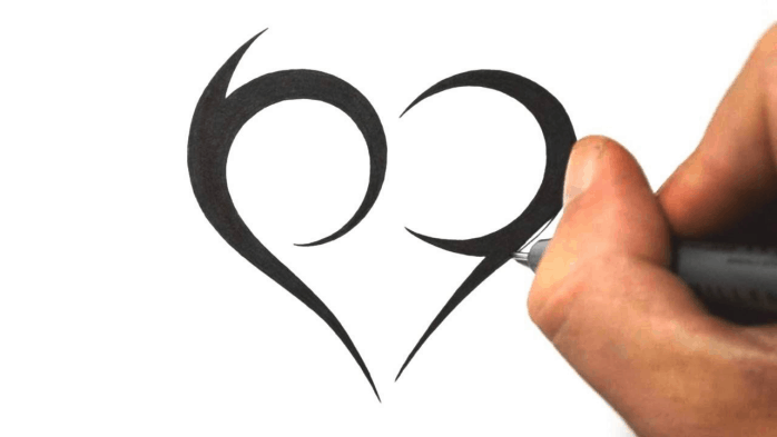 A hand drawing a heart tatoo