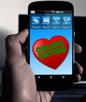 A smartphone held in a hand, showing Online Dating on its screen